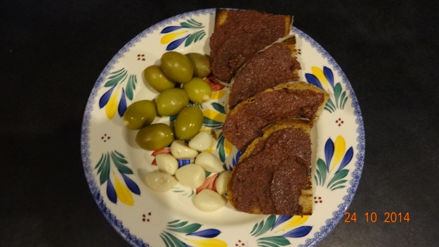 Almond stuffed green olives, pickled garlic, and freshly toasted bread spread with black olive tapenade (olive paste) - yumm!
